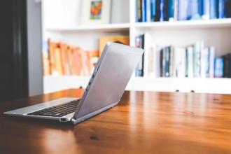 computer on desk in front of bookshelf; working on author website
